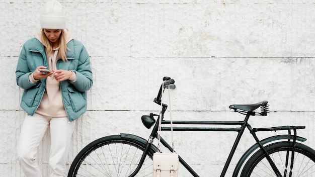 Женщина с ее велосипедом, отдыхая, вид спереди