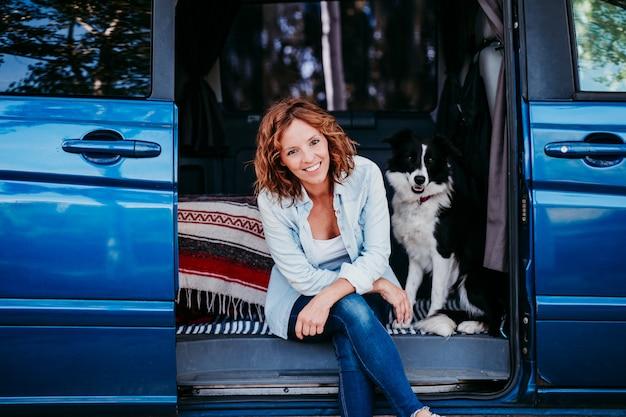 バンで彼女のボーダーコリー犬を持つ女性。旅行のコンセプト