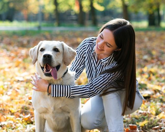 公園で彼女の犬を持つ女性