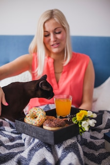 Woman with her cat and breakfast on the bed
