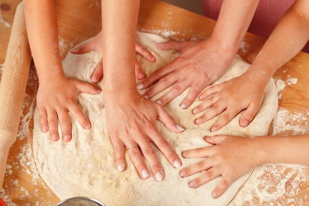 Женщина с детьми замешивает тесто на кухне крупным планом
