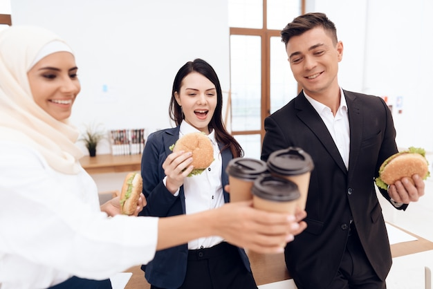 A woman with her colleagues eating a hamburger