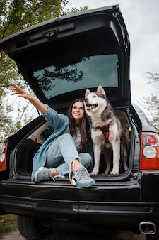 Woman with her cute husky dog traveling by car