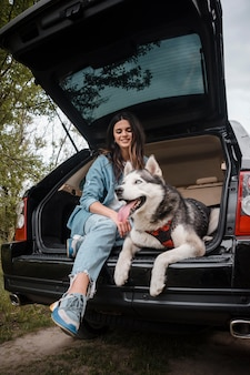 Woman with her cute husky traveling by car