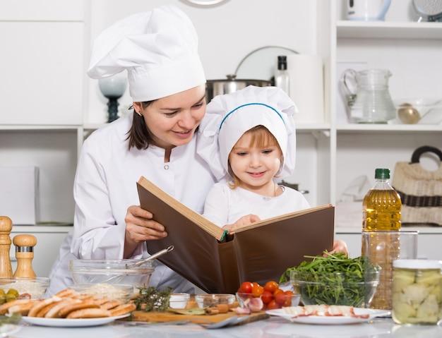 彼女の娘と一緒の女は一緒に料理本でレシピを見ている