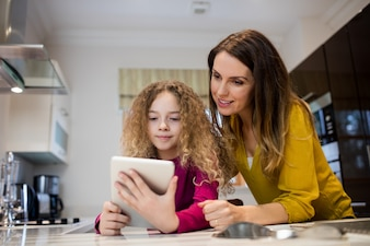 Woman with her daughter looking at a tablet