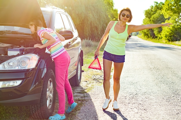 Woman with her daughter near broken car