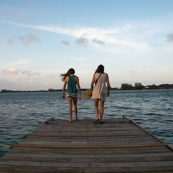 Woman with her daughter standing on a pier and looking at sea, utila island, bay islands, honduras