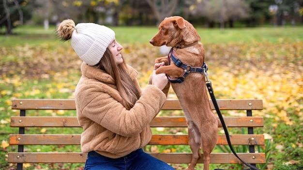 공원에서가 그녀의 강아지와 여자. 여자의 손에 강아지의 발이 있고, 그녀는 그것을보고 웃고 있습니다. 벤치, 잔디