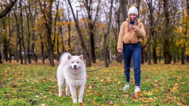공원에서가 그녀의 강아지와 여자. 여자는 그녀의 전화 및 가죽 끈을 잡고 웃고. 주변의 녹지