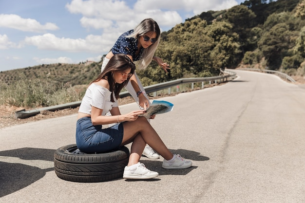 Woman with her female friend sitting on tire looking at map