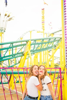Woman with her friend sticking out tongue in front of roller coaster ride