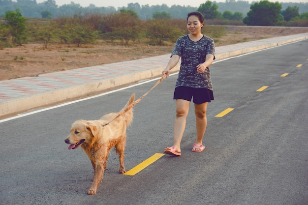 Woman with her golden retriever dog walking on the public road.