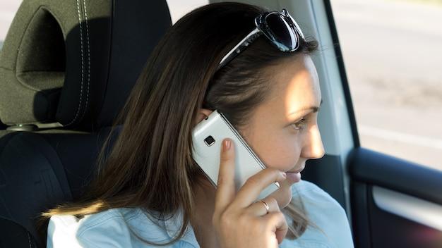 그녀의 머리를 가진 여자는 차에 앉아있는 동안 옆으로 그녀의 휴대 전화로 이야기를 돌렸다