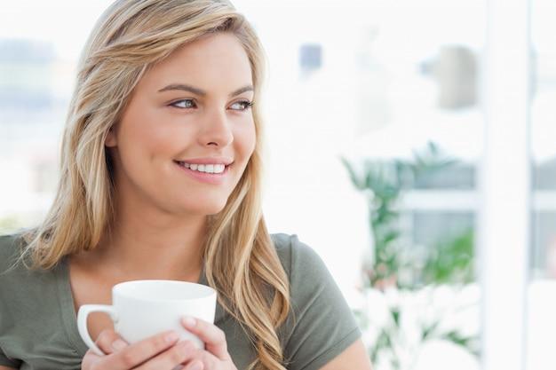彼女の頭のそばにいる女性と手のマグカップ