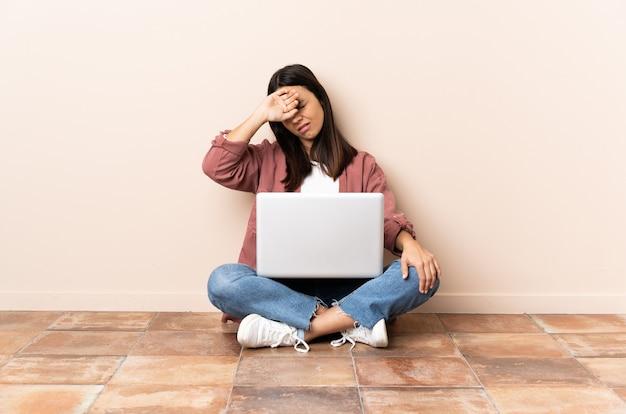 Женщина с ноутбуком сидит на полу