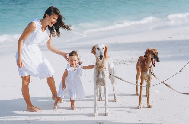 Woman with her little daughter playing with dogs at the beach by the ocean