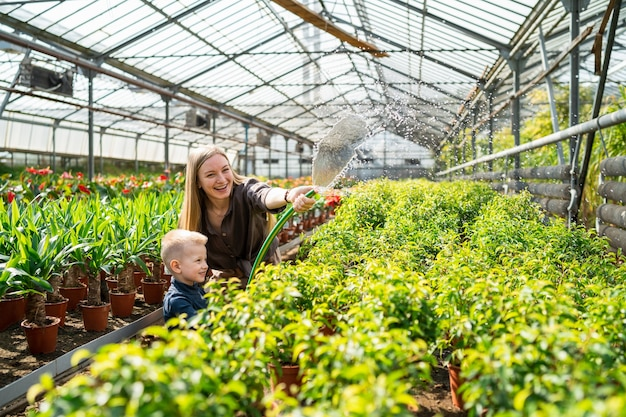 Woman with her little son watering plants in a greenhouse