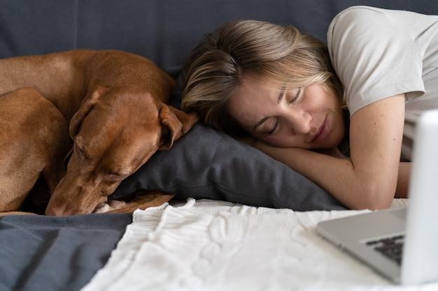 コンピューターで働いた後、自宅のソファの同じ枕で一緒に寝ている愛らしい犬のヴィズラと一緒に寝ている女性。