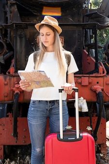 Женщина с багажом смотрит на карту