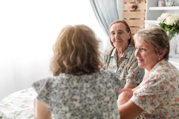彼女の母親とおばあちゃんが台所で一緒に座っている女性