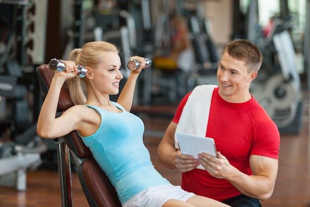Женщина со своим личным тренером по фитнесу в тренажерном зале с гантелями