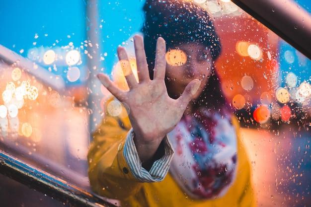 Женщина с ее правой рукой на влажном стекле