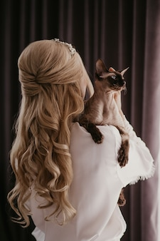 Woman with her sphynx cat in her hands