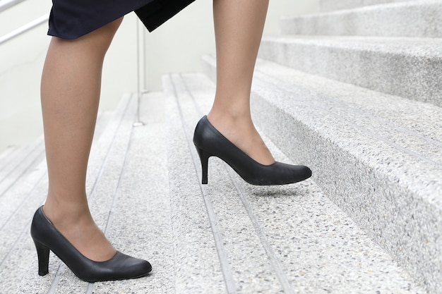 階段を上っているハイヒールの靴を持つ女性