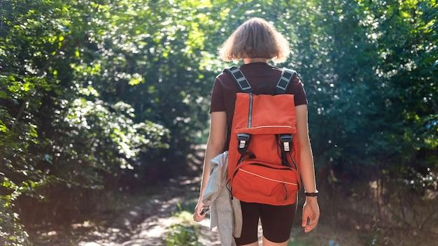 森の中のトレイルでバックパックをハイキングする女性
