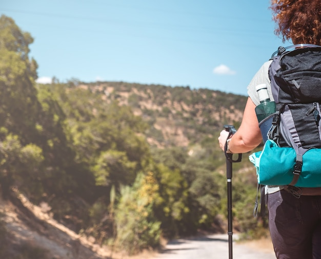 Woman with hiking equipment walking in green mountain landscape on a sunny day