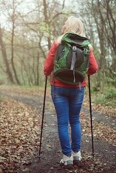 森の中のハイキングポールを持つ女性