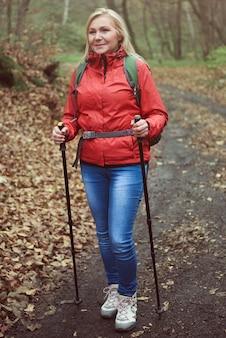 Женщина с походными палками на лесной тропе