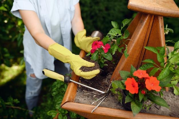 庭の花壇でくわを持つ女性