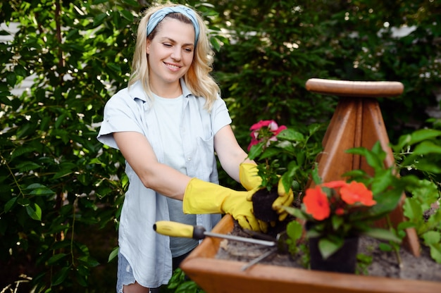 Woman with hoe at the flowerbed in the garden. female gardener takes care of plants outdoor, gardening hobby, florist lifestyle
