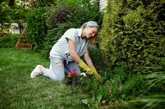 Woman with hoe grows flowers in the garden. female gardener takes care of plants outdoor, gardening hobby, florist lifestyle and leisure