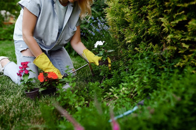 Woman with hoe grows flowers in the garden