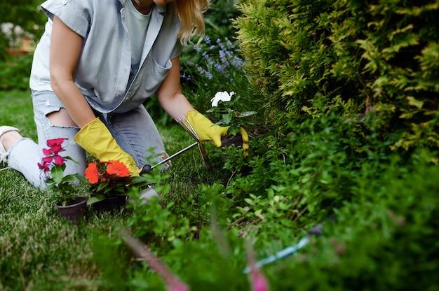 鍬を持つ女性は庭で花を育てる