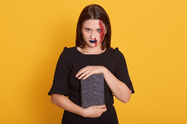 Woman with horror halloween make up and bloody wound posing in studio on yellow, young female with dengerous sight holds book with incantation, dresses black dress