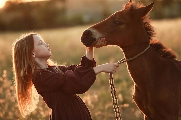 馬を持つ女性は草のフィールドでクローズアップ