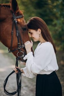 森の中で馬を持つ女性