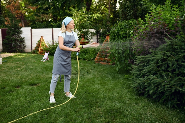 Woman with hose watering flowers in the garden. female gardener takes care of plants outdoor, gardening hobby, florist lifestyle and leisure