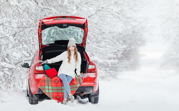 雪の降る冬の日に赤い車に座ってホットコーヒーを手に女性
