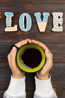 Woman with hot cup of coffee, with biscuits. love concept. love word with coffee