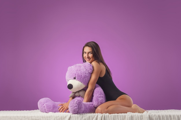 Woman with a huge teddy bear on the bed