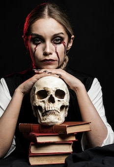 Woman with human cranium and books
