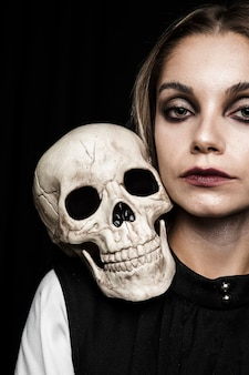 Woman with human skull on shoulder