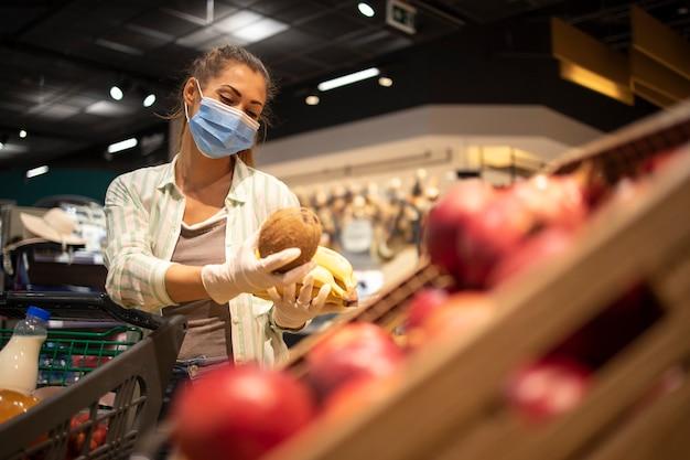 코로나 바이러스 기간 동안 과일을 구입하고 유행성 격리를 준비하는 식료품 점에서 위생 마스크와 고무 장갑 및 장바구니를 가진 여성