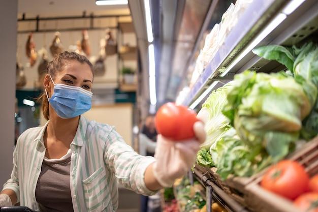 コロナウイルスの間に野菜を購入し、パンデミック検疫の準備をしている食料品店で衛生的なマスクとゴム手袋とショッピングカートを持っている女性