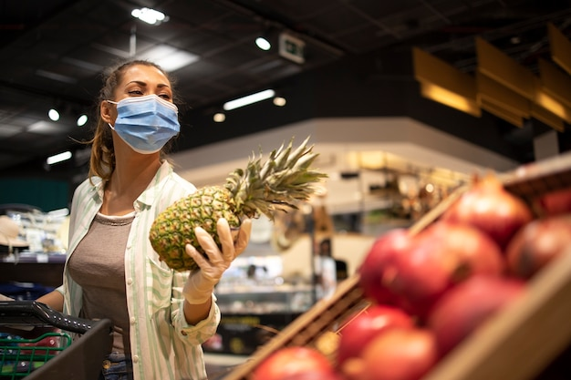 Woman with hygienic mask and rubber gloves and shopping cart in grocery buying fruit during corona virus and preparing for a pandemic quarantine